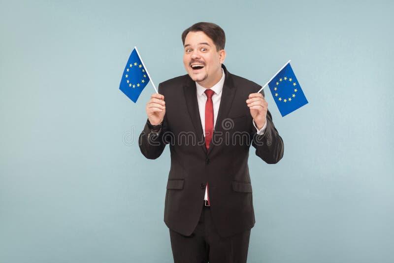 欧洲政客举行旗子和暴牙微笑 免版税库存照片