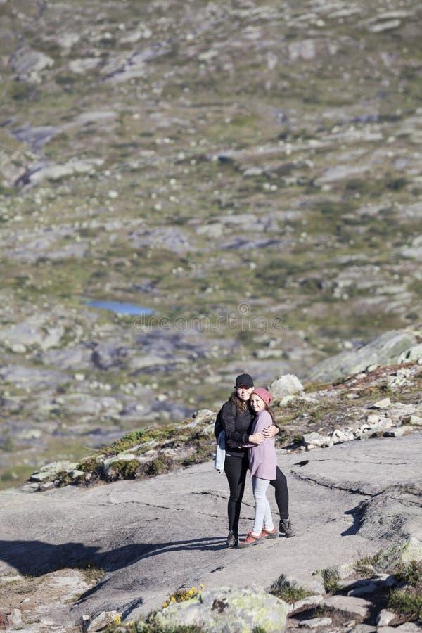 欧洲母亲拥抱的少年女儿,站立在岩石在远足在路线期间对trolltunga,拷贝空间 ?? 免版税图库摄影