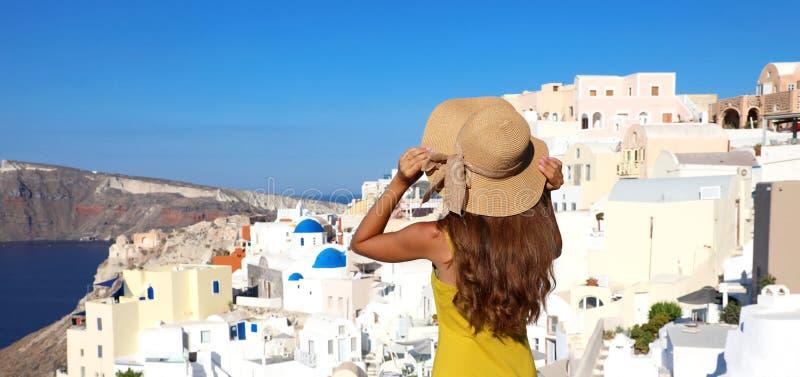 欧洲游客旅行妇女从Oia,圣托里尼,希腊的全景横幅 塑造看著名蓝色圆顶教会的少妇 免版税库存图片