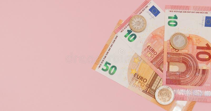 欧洲金钱:钞票和硬币特写镜头在桃红色背景 到达天空的企业概念金黄回归键所有权 免版税库存图片
