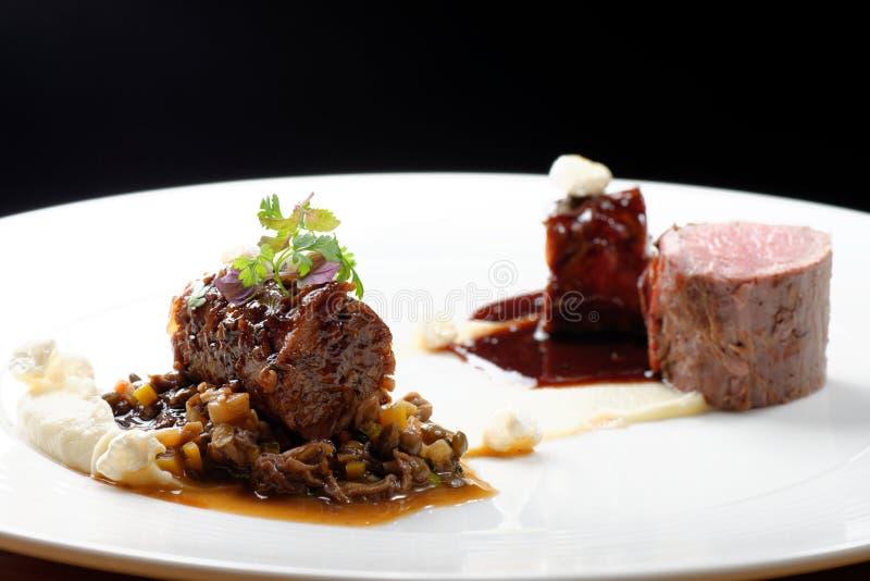 欧特烹调,烤小牛肉里脊肉牛排,小牛肉尾巴用口岸,羊肚菌,扁豆调味汁  免版税图库摄影