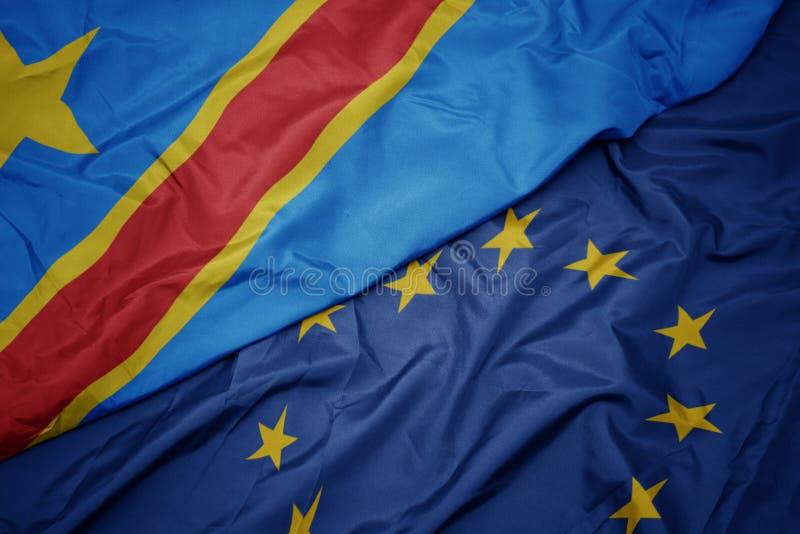 欧盟挥动的五颜六色的刚果民主共和国的旗子和旗子 免版税库存照片