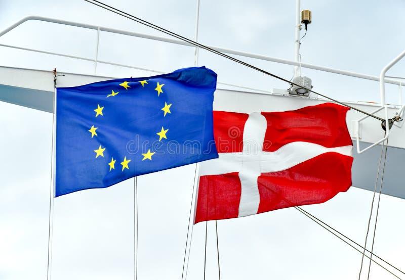 欧盟的旗子和丹麦的状态肩并肩船的帆柱的 免版税库存图片