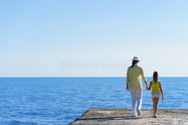 欧洲人怀孕的妈妈和她的小女儿在防堤走到蓝色海在握每othe的手的清楚的天空下 免版税库存照片