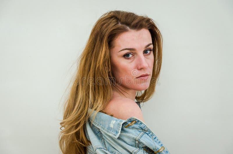 欧洲出现的年轻美丽的女孩与摆在色情性感的姿势的长的头发的露胸部,盖用在blac的一件牛仔布夹克 免版税库存照片
