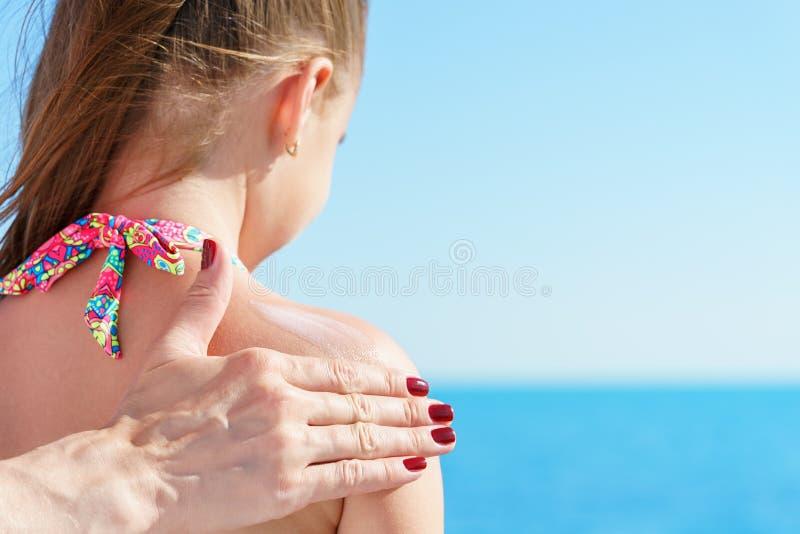 欧洲妈妈应用太阳保护者奶油在她的海滩的年轻俏丽的女儿肩膀接近热带绿松石se 免版税库存图片