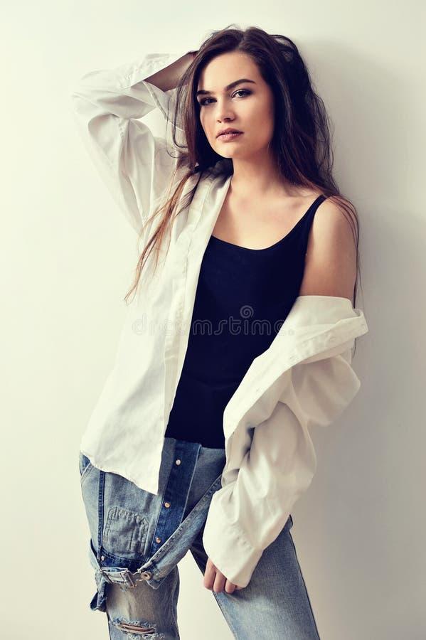 年轻欧洲有吸引力的时装模特儿在牛仔裤总体和衬衣摆在 库存照片