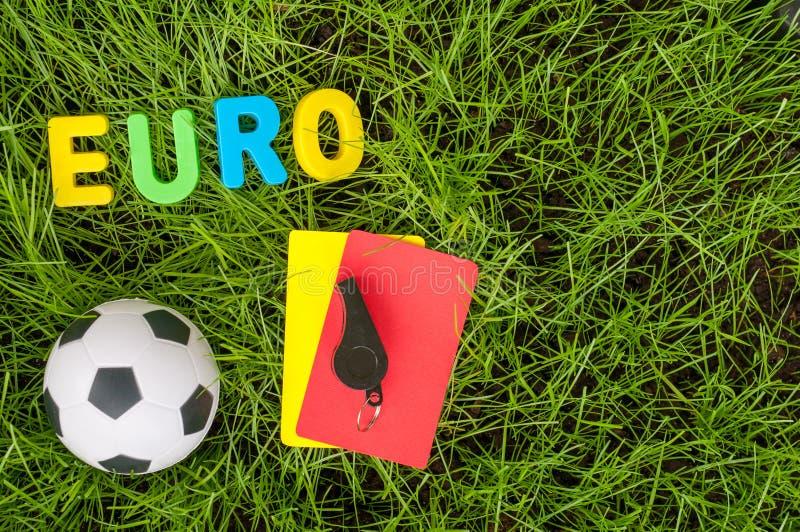 欧洲橄榄球冠军-与球的图象,担任仲裁在绿色草坪的黄色,红牌 足球和公平比赛的标志 图库摄影