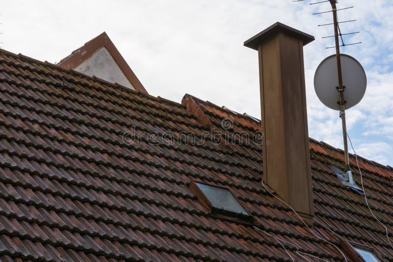 欧洲橙色瓦烟囱卫星盘住宅Ro 免版税库存图片