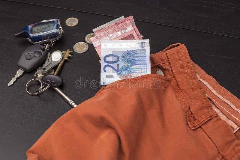 欧洲纸币和硬币下降了在他的在桌上的口袋外面,在上谎言钥匙 免版税图库摄影