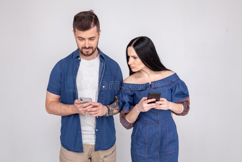 欺诈和失真 暗中侦察和偷看在她的男朋友智能手机,白色背景的女孩 免版税库存图片