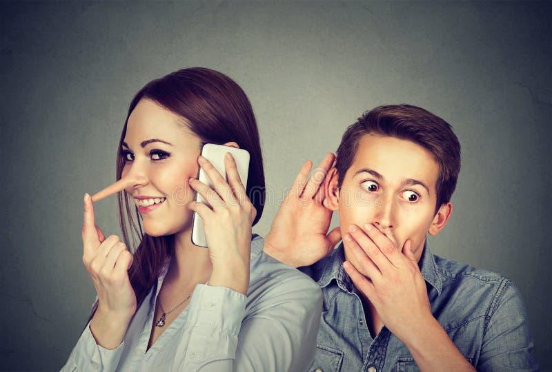 欺诈的女朋友 供以人员听妇女说谎者谈话在有她的恋人的手机 免版税库存图片