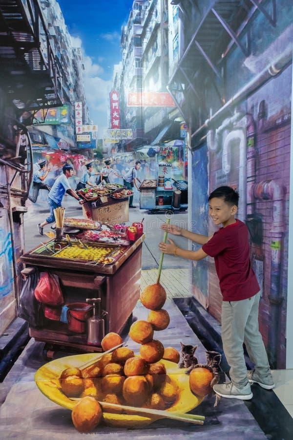 欺骗与塑造为照片的年轻男孩的艺术都市中国街道fayre 库存图片