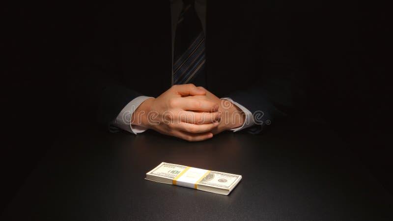 贿款:商人在二人一桌的美元上等待并且把金钱放- 免版税库存图片