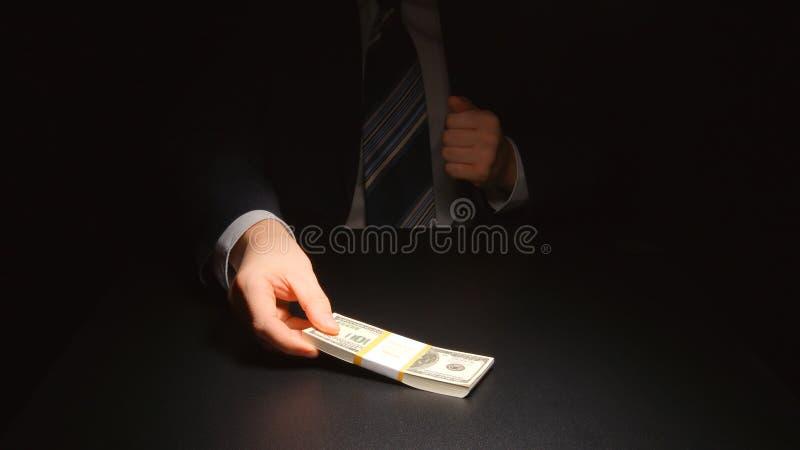 贿款:商人去掉从衣服美元的一个口袋的金钱 免版税图库摄影
