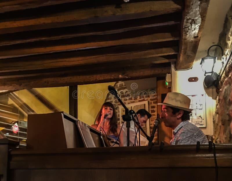 歌手和钢琴演奏家在巴黎咖啡馆招待 库存图片