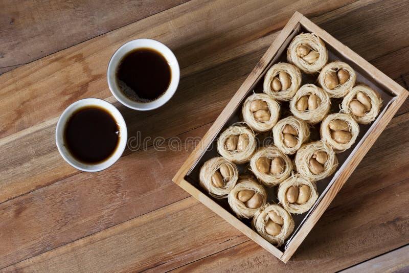 歌手巢knafeh -一份中东甜盘aysh el bolbol和阿拉伯咖啡Qahwah有木背景 库存图片