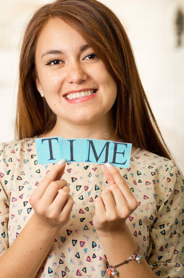 阻止小字母的特写迷人的深色的妇女拼写字时间和微笑对照相机 免版税库存图片