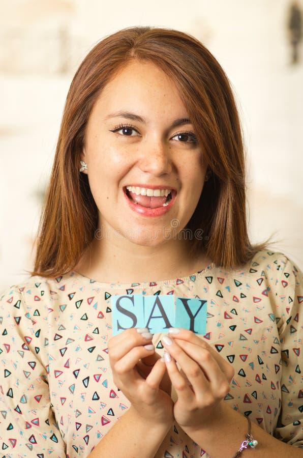 阻止小字母的特写迷人的深色的妇女拼写词说和微笑对照相机 库存图片