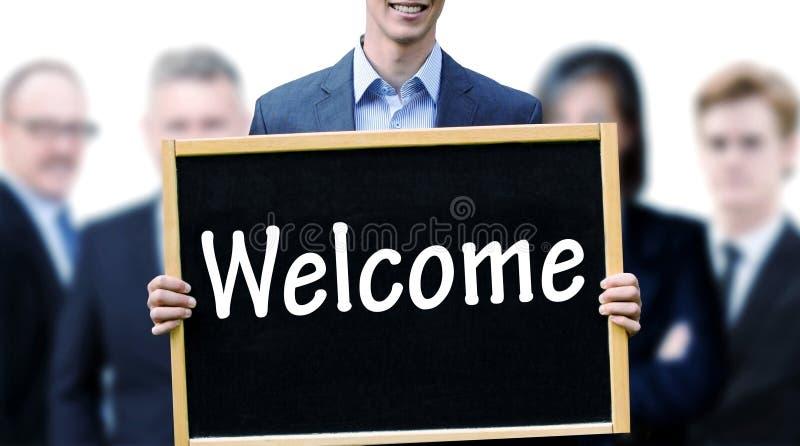 阻止有词欢迎的年轻商人一个黑板 免版税图库摄影
