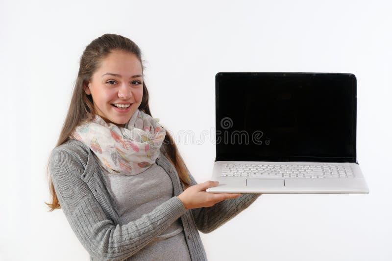 阻止膝上型计算机和smil的一个美丽的少妇的画象 库存照片