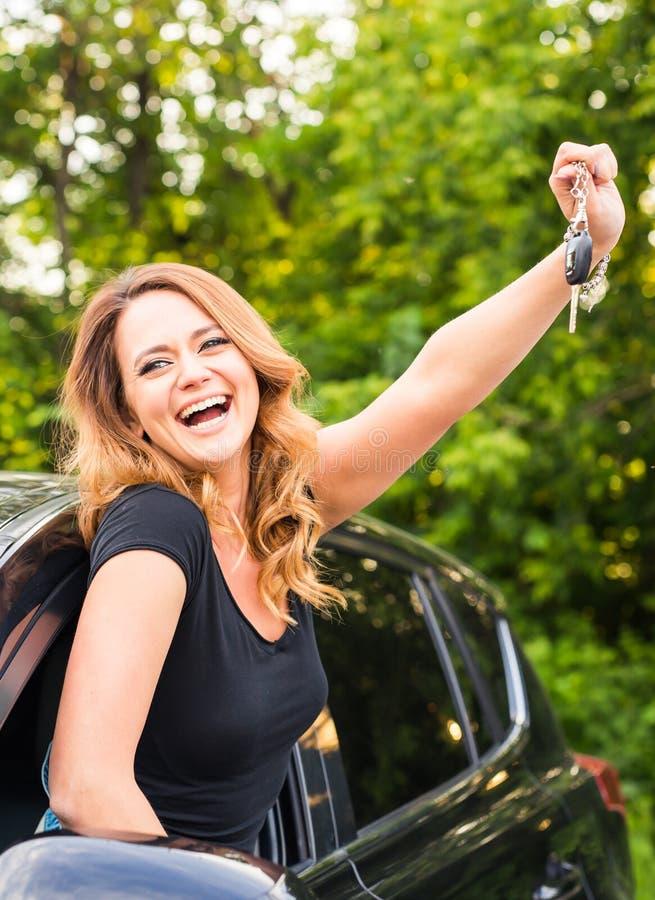 阻止钥匙的年轻快乐的快乐的微笑的华美的妇女对她的第一辆新的汽车 用户满意 库存照片