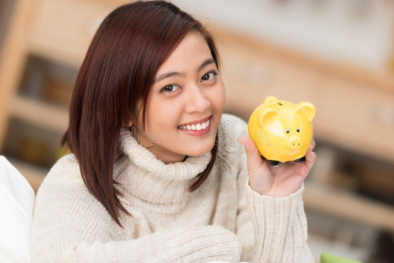 阻止黄色存钱罐的微笑的妇女 免版税库存照片