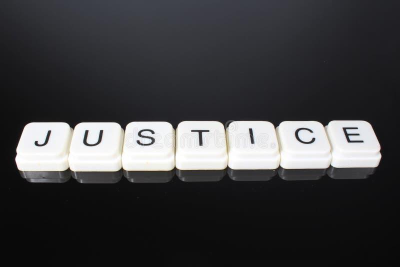 正义文本词标题说明标签盖子背景背景 字母表信件在黑反射性背景的玩具块 空白 图库摄影