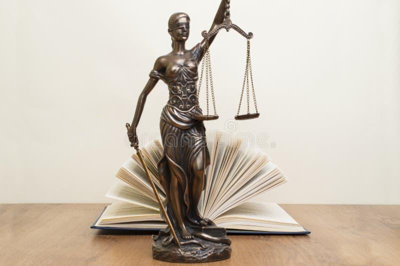 正义雕象在木桌上的以一本开放书为背景 免版税图库摄影