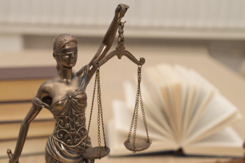 正义雕象在木桌上的以一本开放书为背景 免版税库存图片