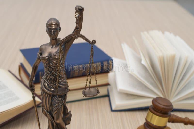 正义雕象在木桌上的以一本开放书为背景 图库摄影