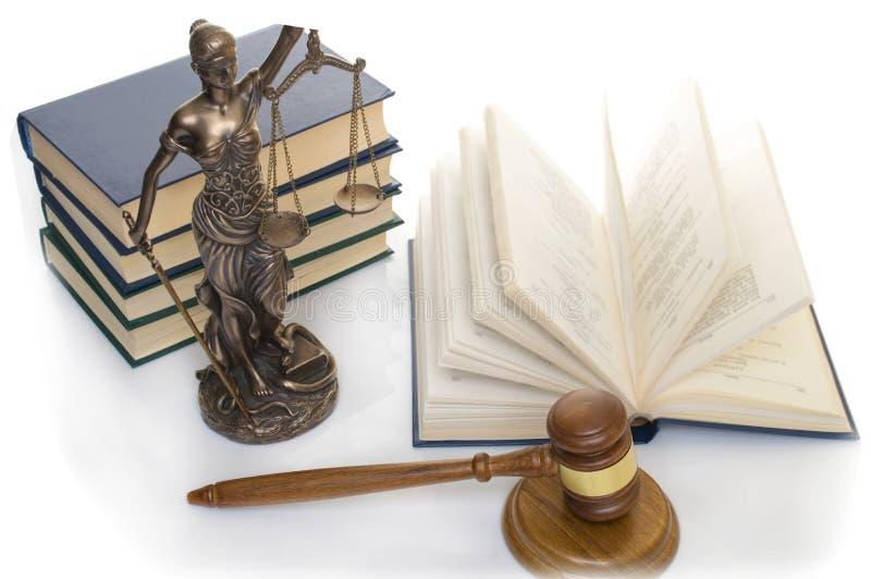正义雕象在木桌上的以一本开放书为背景 库存照片