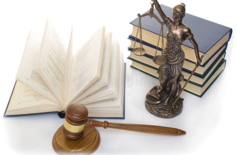 正义雕象在木桌上的以一本开放书为背景 库存图片