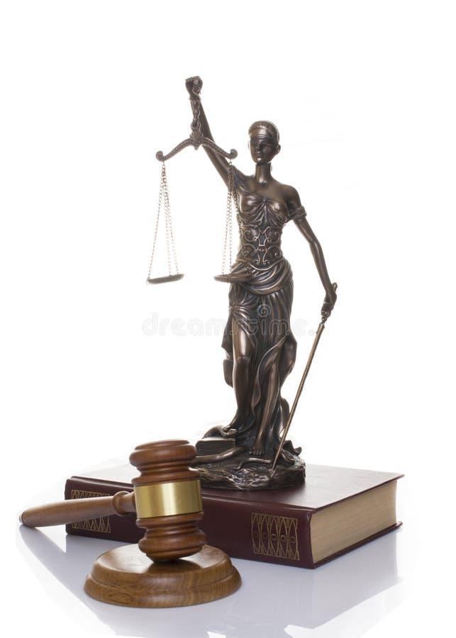 正义,在书后的法官的锤子雕象在白色背景 库存图片