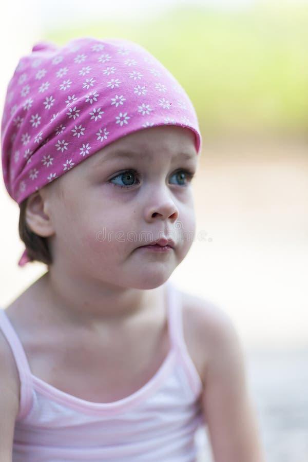 正在寻找某人或某事的逗人喜爱的矮小的沉思女孩 免版税库存照片