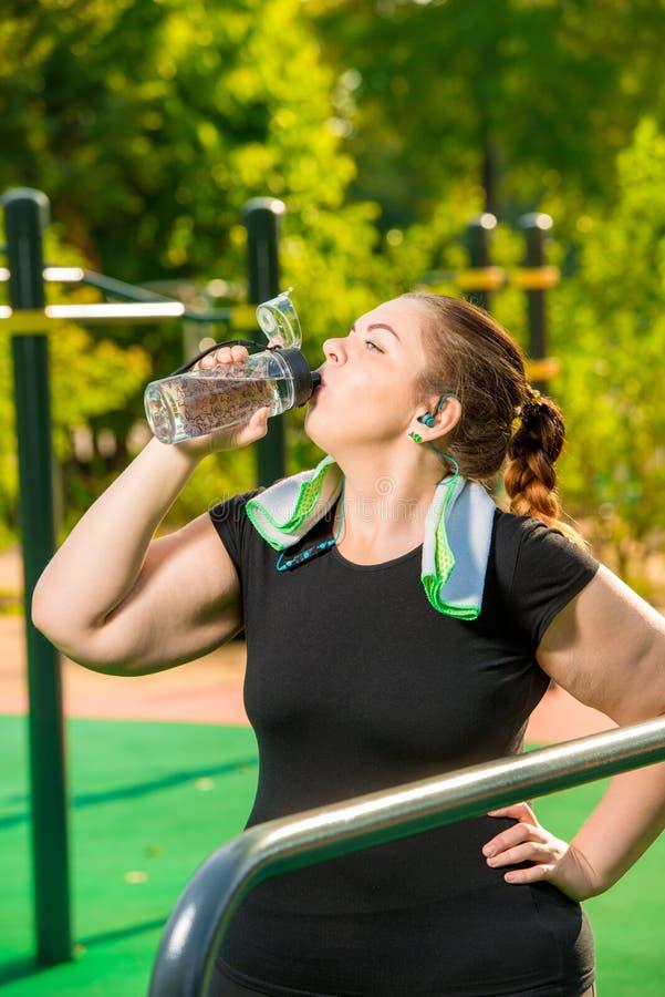 正大小女孩在体育活动以后喝从瓶的净水 库存照片
