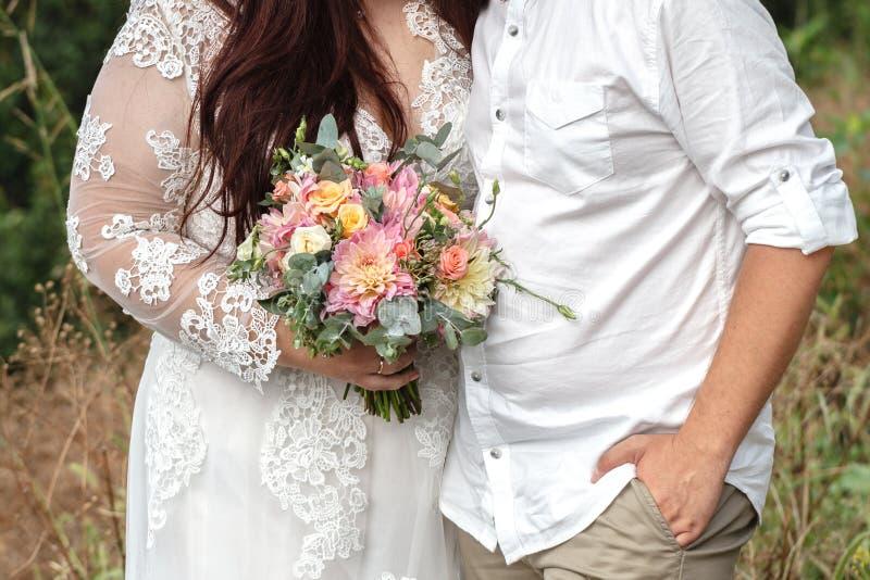 正大小婚礼夫妇是站立和拥抱外面 弯曲 免版税库存图片