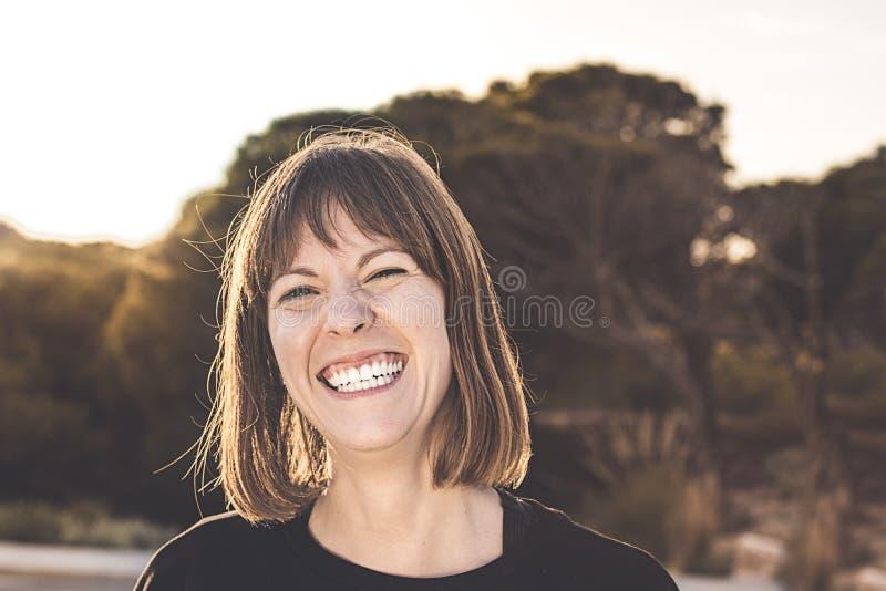 正常深色女孩微笑 有微笑的妇女在日落 免版税库存照片
