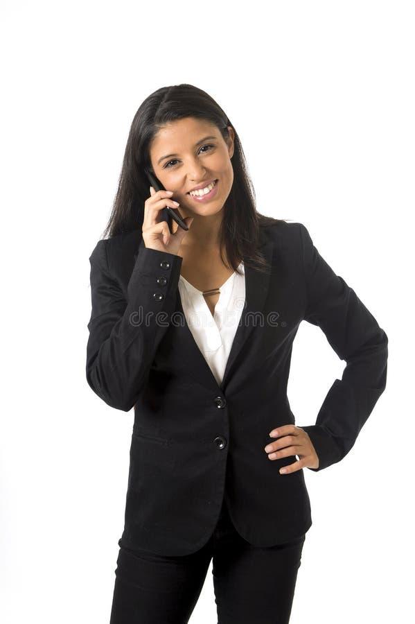 正式办公室衣服微笑的愉快谈话的可爱的拉丁女实业家在手机 图库摄影