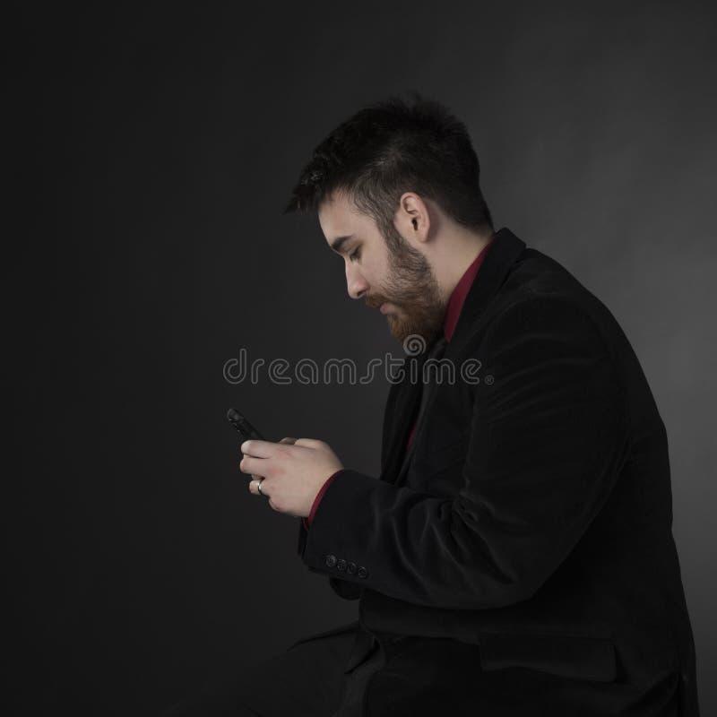 正式服装的人有在侧视图的电话的 库存图片