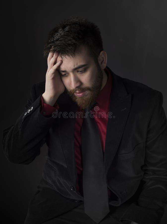 正式服装遭受的头疼的年轻人 免版税库存图片