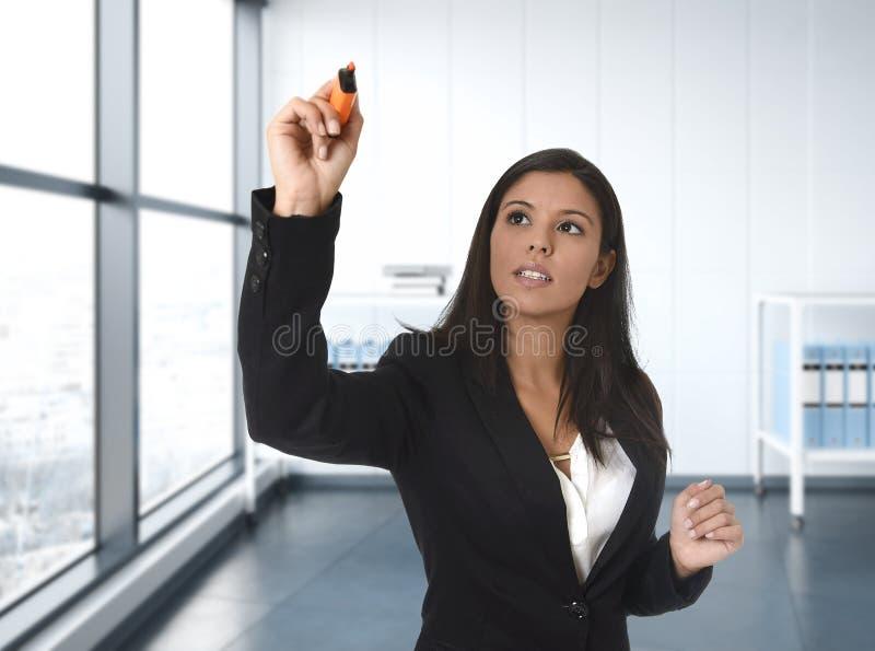 正式衣服文字的拉丁女商人与在无形的虚屏上的标志或委员会在现代办公室 免版税库存照片