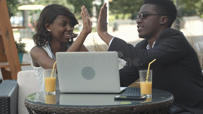 正式衣服的非洲人解释经营战略的对他的使用膝上型计算机的非洲女性同事在会议期间 免版税库存照片