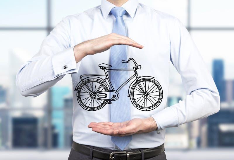 正式衣裳的一个人拿着在他的手之间的一辆速写的自行车 免版税库存图片