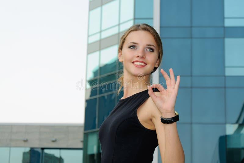 正式衣裳的女商人显示姿态ok 库存照片