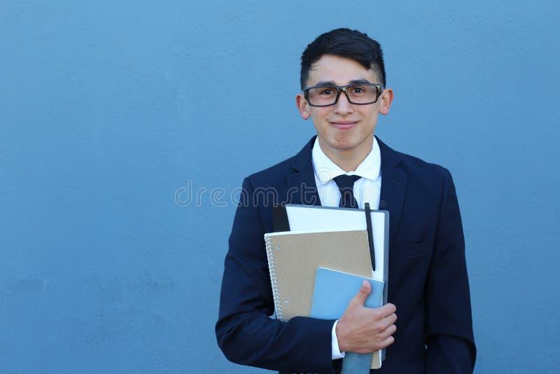 正式高中制服的逗人喜爱的少年男孩拿着笔记本微笑与拷贝空间佩带的玻璃的 库存照片