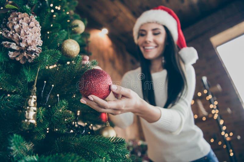 正性开朗女孩低角照片悬挂红色圣诞宝布准备常青树参加x-mas时间派对 免版税库存照片