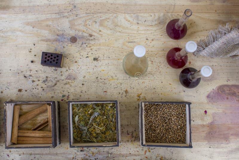 正方形木箱用各种各样的明亮的色的香料和古色古香的玻璃瓶有液体的在台式视图 库存图片