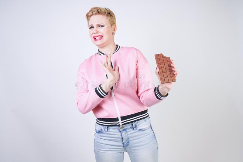 正有短的理发立场的大小白种人女孩在有巧克力块的桃红色粗呢夹克在她的手上和展示恨情感f 免版税图库摄影