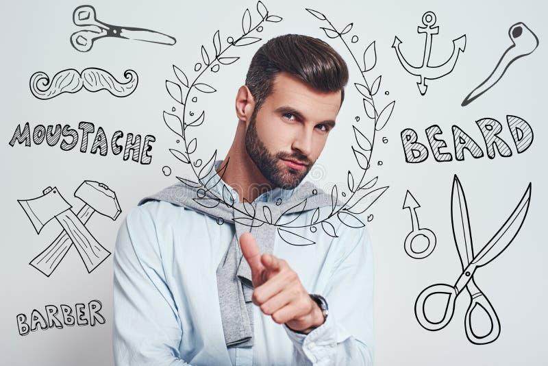 正确的选择 有完善的发型的迷人的有胡子的人打手势和看照相机的,当站立反对灰色时 免版税库存图片